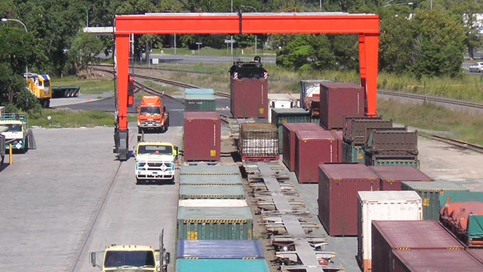 Isoloader Rubber Tired Gantries (RTG) used for train stripping and container storage in intermodal terminals.